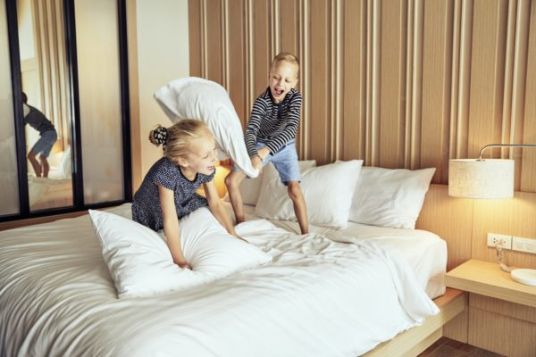 Laughing little boy having a pillow fight with his sister