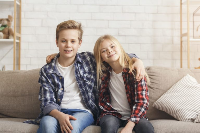 Brother And Sister Embracing Smiling Sitting On Couch At Home