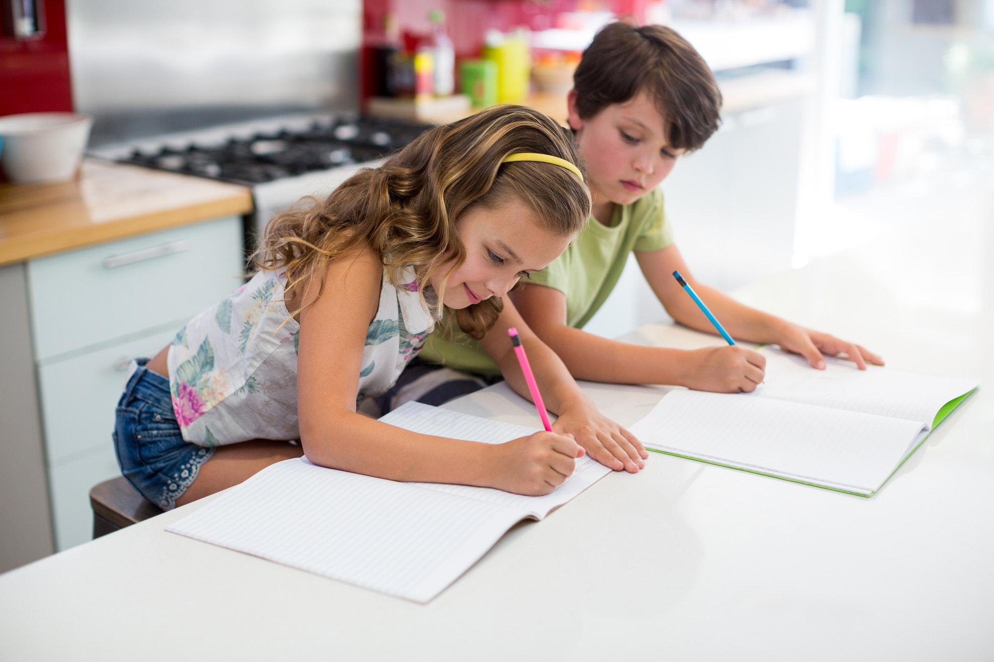 Siblings doing homework in kitchen